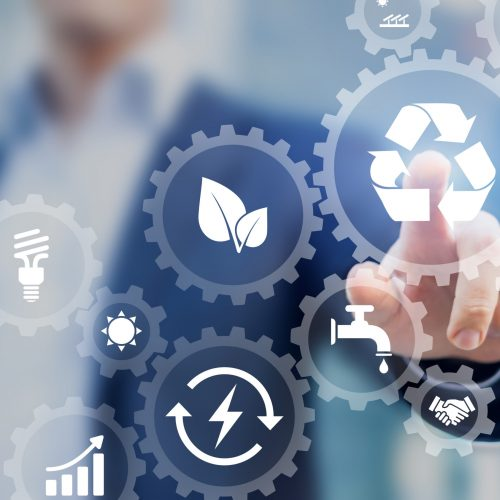 Sustainable development concept on screen with icons of renewable energy, natural resources preservation, environment protection inside connected gears, business person in background